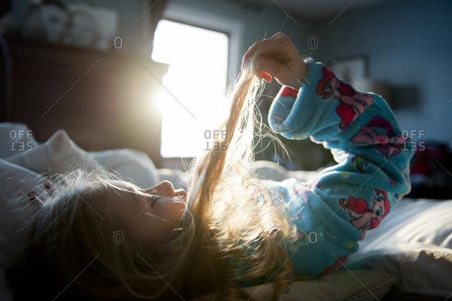 Little girl lying in bed lifting strands of hair