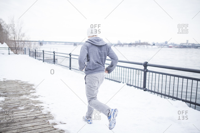 Young man working out along a snowy waterfront
