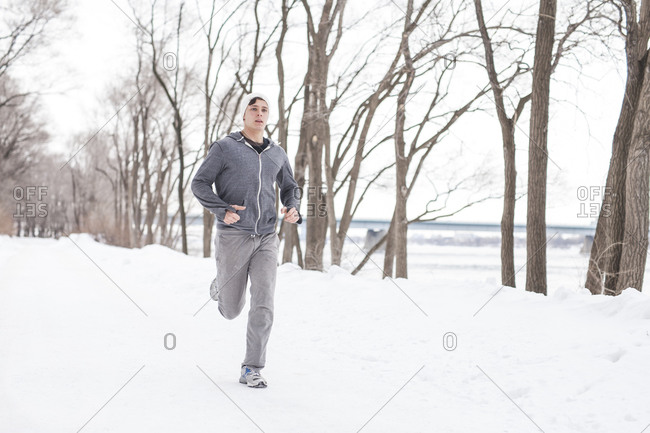 Young man running in snow along a waterfront
