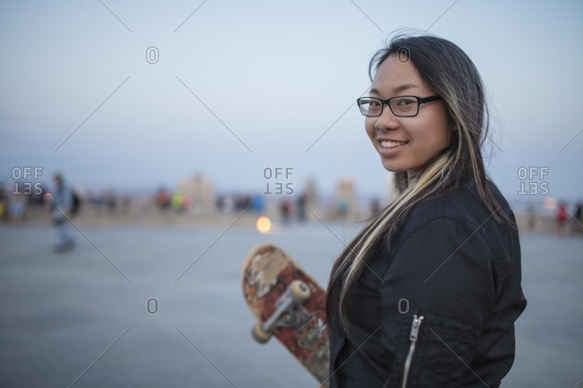 Young woman standing in a skateboarding park at dusk