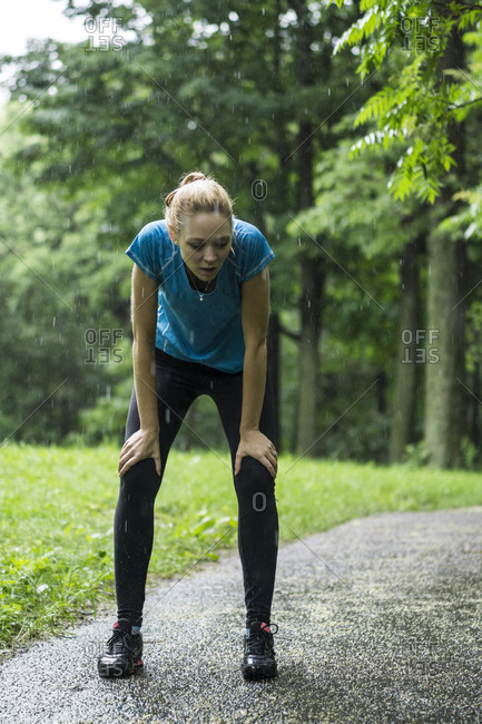 Young woman resting during a jog in the rain