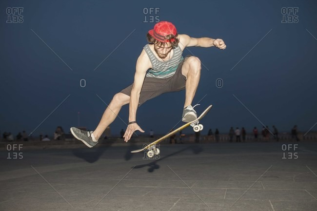 Young skateboarder flipping his board at a skate park night