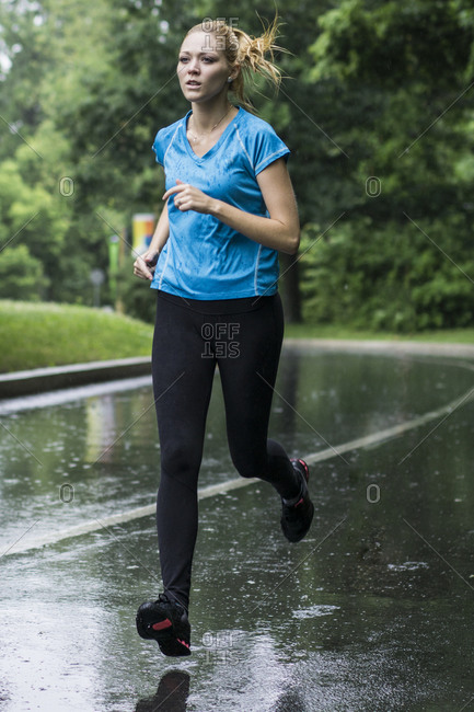 Young woman jogging in the summer rain