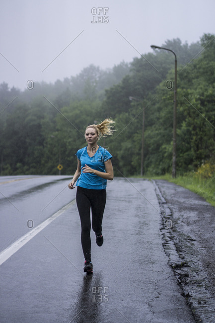 Young woman jogging in the rain along a highway