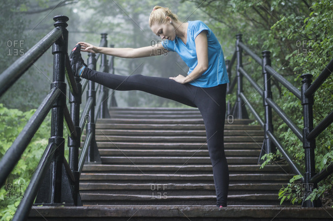 Young woman stretching on stairs during a workout on a rainy day