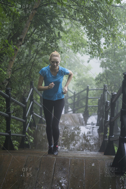 Young woman running up stairs during a workout on a rainy day