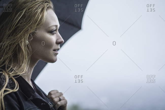 Portrait of a woman holding an umbrella on a foggy day