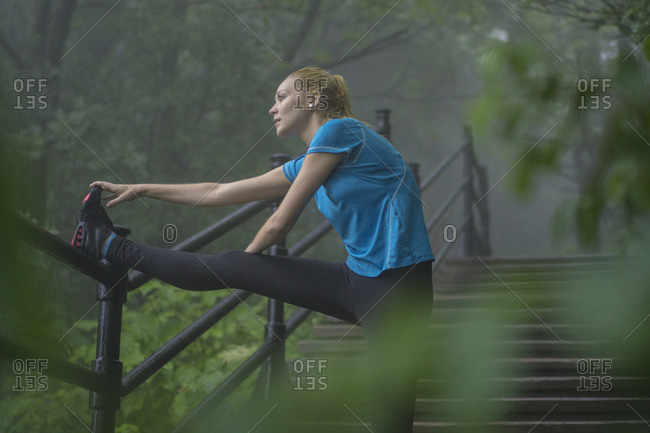 Young woman using stairs to stretch during a rainy day workout