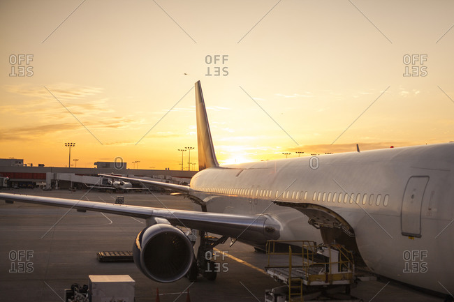 Airplane parked on a tarmac at sunset