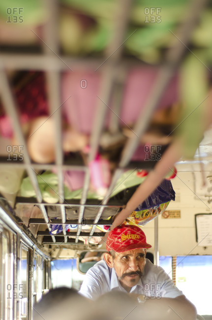 Nicaragua- January 15, 2013: Man propped on the back of a seat in a chicken bus