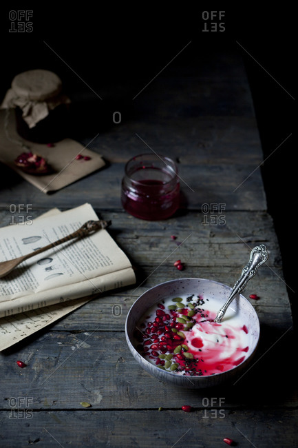 Bowl with yogurt, seeds and red fruit syrup on table with a book