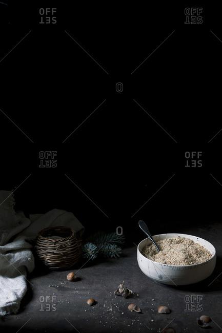 Bowl of hazelnut flour with hazelnut shells on dark background