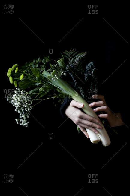 Hands holding a bouquet of vegetables and wildflowers on a black background