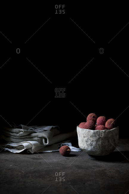 Handcrafted pottery bowl full of lychees (Litchi chinensis), on black background