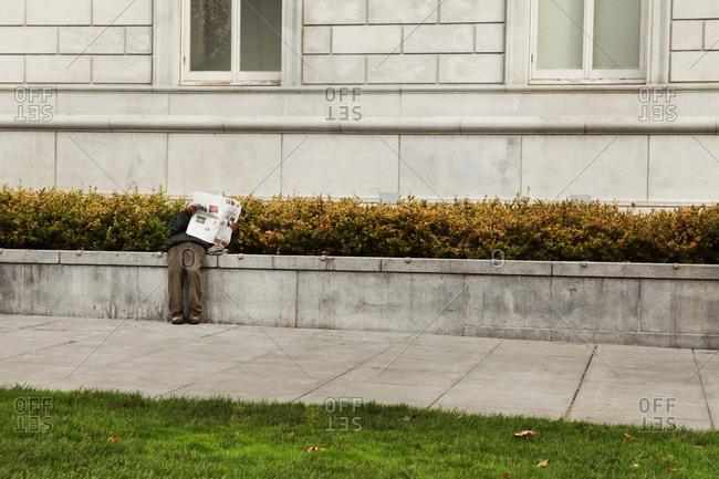 Homeless man reading a newspaper