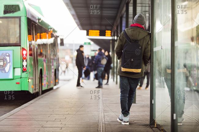 Rear view of man waiting at a bus stop