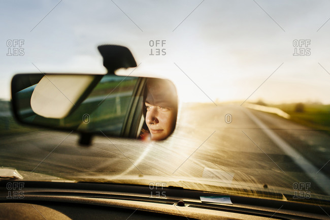 Reflection of a woman in a rear view mirror