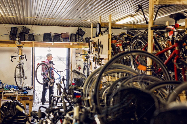 Man carrying a bicycle out of his bike repair shop stock