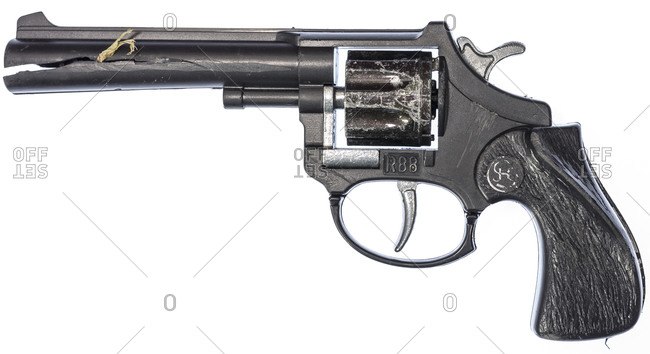 Broken and lost toy gun on a white background