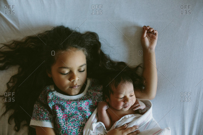 Girl napping with newborn