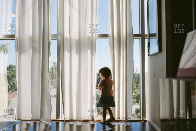 Girl by large sunlit windows