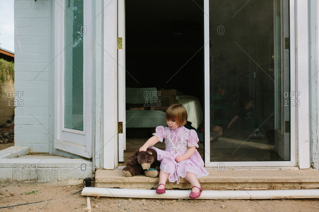 Girl with doll on doorstep