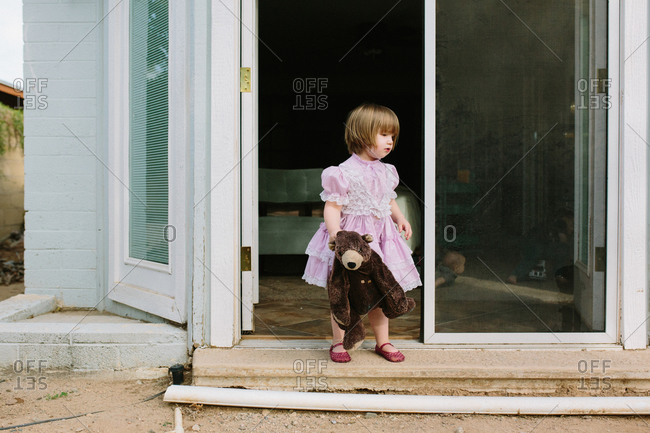 Girl with her doll on doorstep