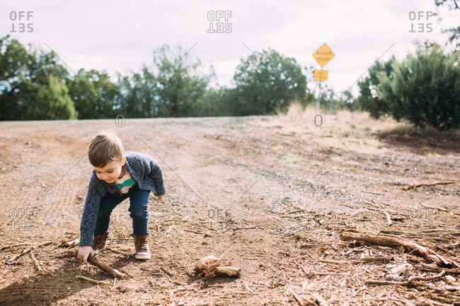 Boy collecting stick on dirt road