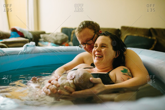 Joyful parents in birthing tub
