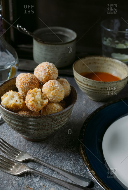 Risotto bon bons and dipping sauce in earthenware bowls