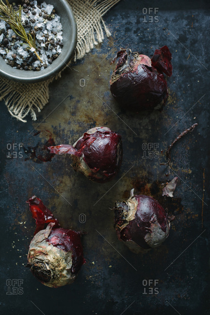 Peeling roasted beets on a weathered surface