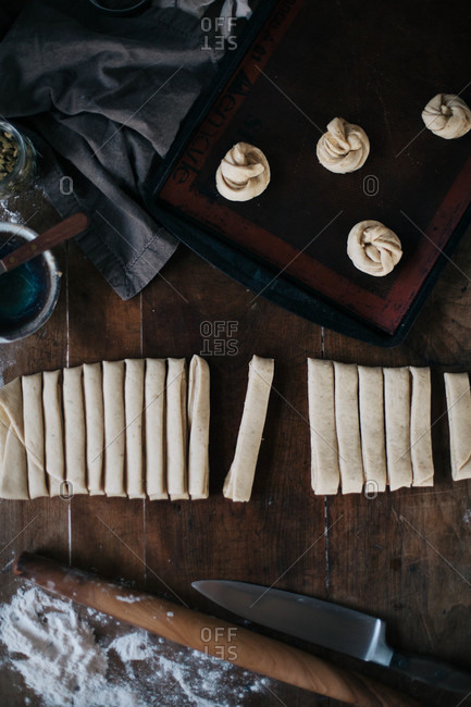 Cinnamon buns being cut, rolled and arranged on a baking pan