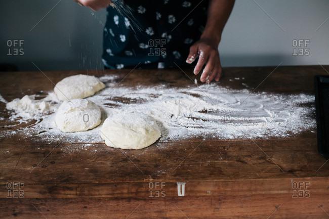 Person sprinkling flour onto balls of dough for pizza