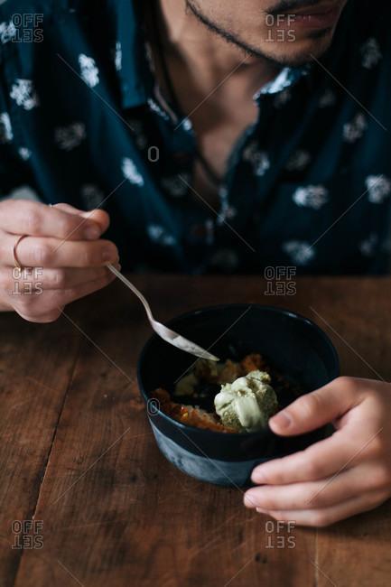 Man eating bowl of dessert