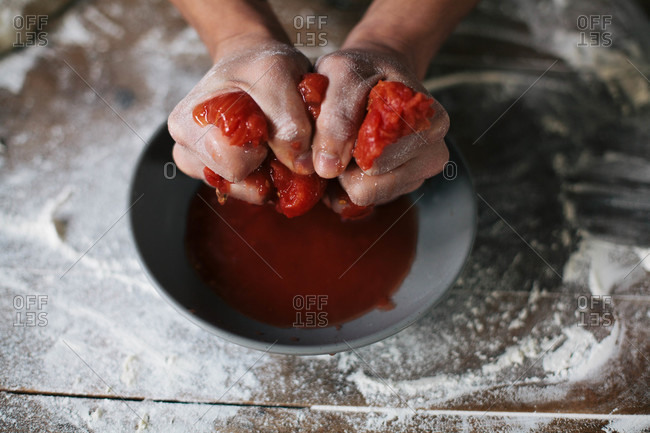 Hands squeezing tomatoes into a bowl for pizza sauce