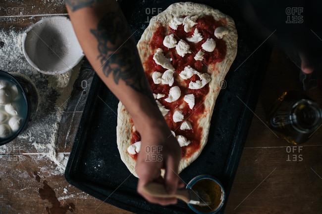 Overhead view of person making homemade pizza