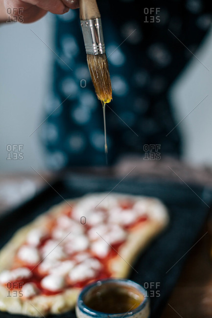 Olive oil dripping from basting brush while making pizza