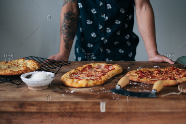 Person standing by three homemade pizzas