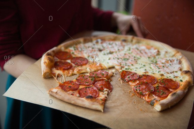 Woman holding a whole pizza
