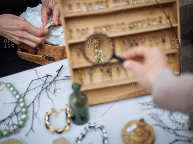 Person magnifying items on a table at an outdoor market