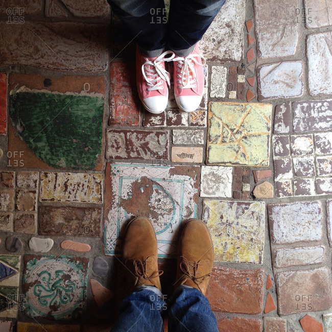 Overhead view of two pairs of shoes on a colorful tile floor