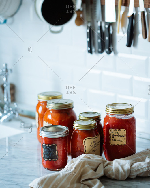 Homemade jars of tomato sauce on a kitchen countertop