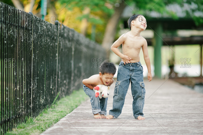 Brothers standing on a wooden pier laughing