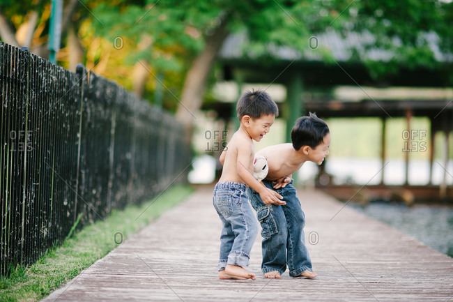 Two brothers standing on a pier laughing together