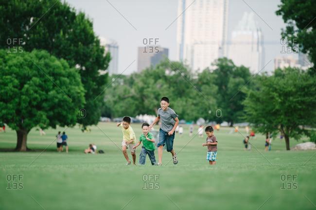 Boys running across a green field in a park