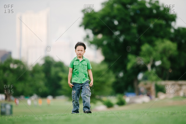 Little boy standing in a park crying