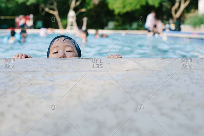 Little boy peeping over the edge of a pool
