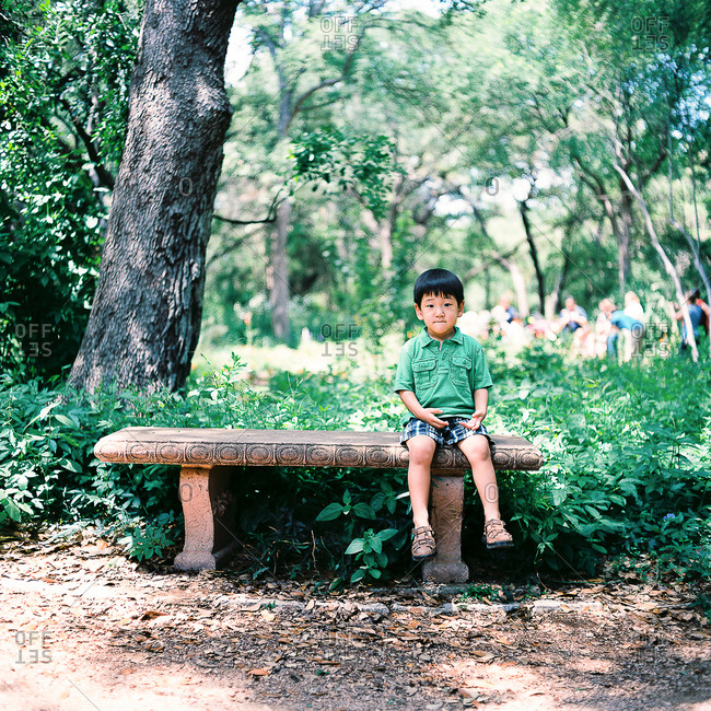 Little boy sitting on a cement bench in a park