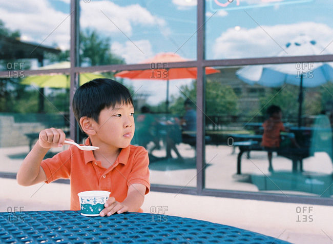 Little boy sitting at an outdoor table eating ice cream