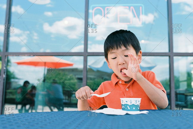 Little boy eating ice cream and licking his fingers